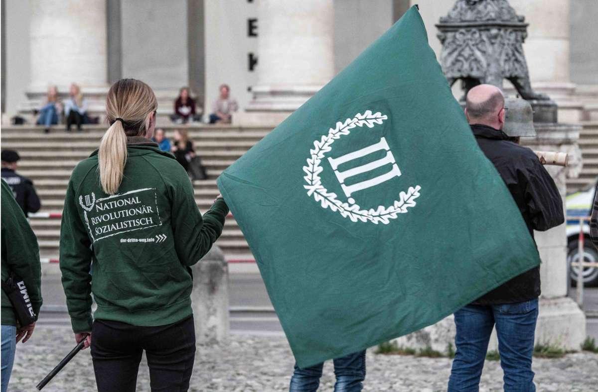 """Eine Frau demonstriert in München ihre Zugehörigkeit zur rechtsextremen Gruppe """"Der III. Weg"""". (Archivbild) Foto: imago images/ZUMA Wire/Sachelle Babbar"""
