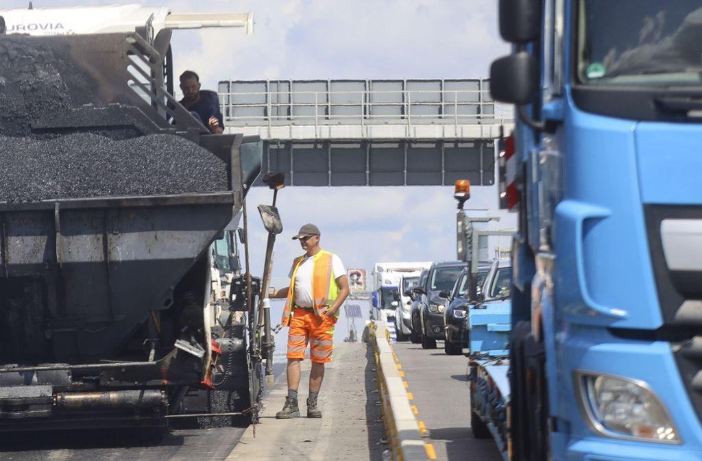 Ganz schön knapp: Dass hinter ihnen die Lkw vorbeidonnern, beeindruckt die Bauarbeiter am Asphaltfertiger nicht mehr. Foto:factum/Granville Foto:
