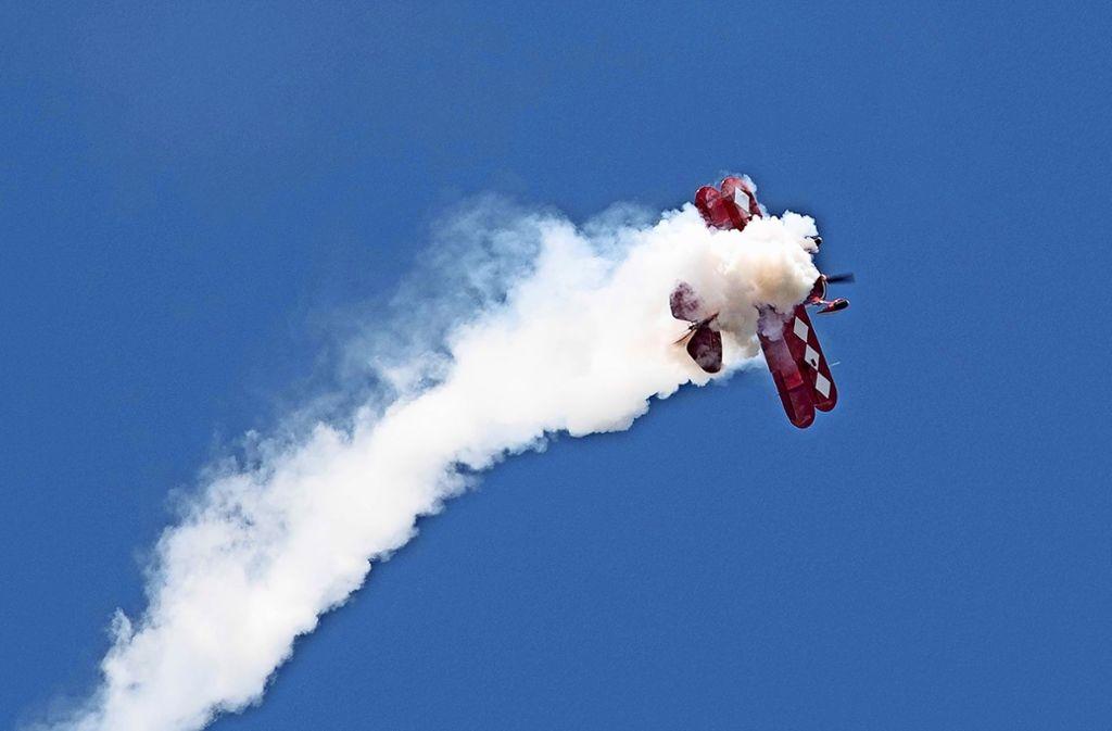 Während die Segelflieger rote  Rauchfahnen ausstoßen,   hinterlässtPetra Unger mit ihrem Motorkunstflieger hier lauter weiße Schwaden. Foto: Rudel/Hass
