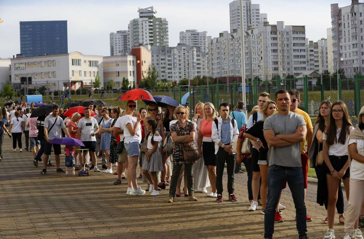 Belarus, Minsk: Menschen stehen auf einem Gehweg an einem Wahllokal Schlange. Foto: dpa/Sergei Grits