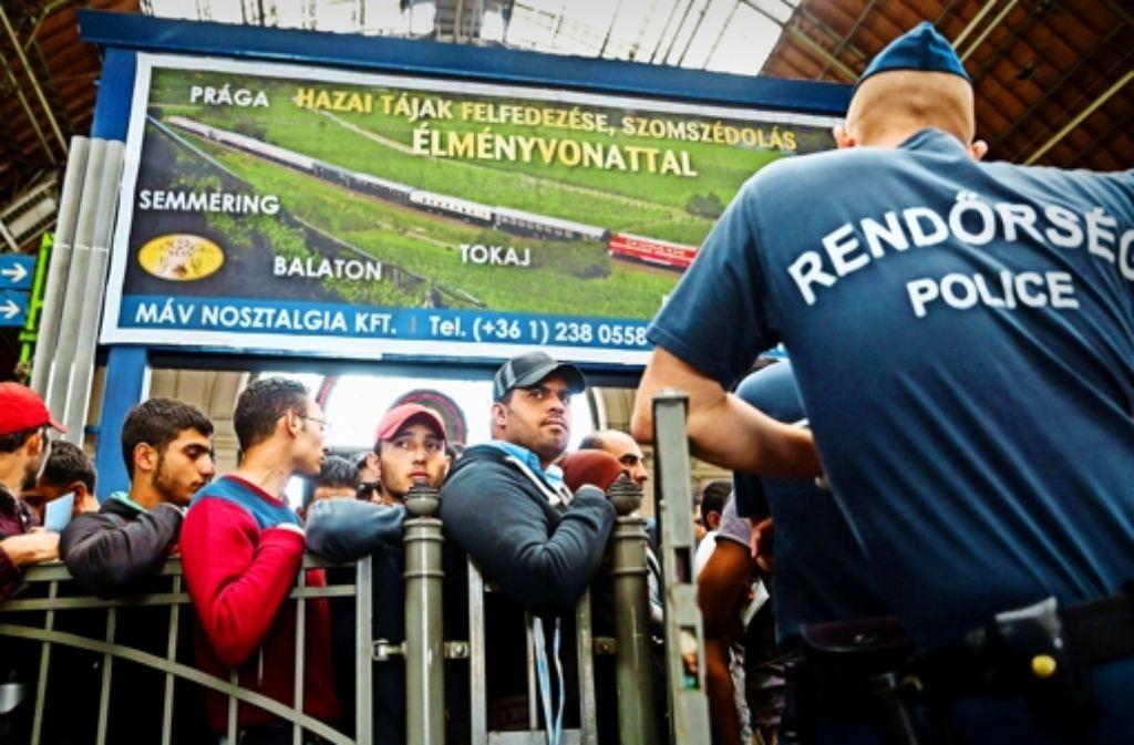 Die Staatsmacht beschränkt sich am Budapester Bahnhof Keleti eher darauf, die Flüchtlinge unter Kontrolle zu halten. Foto: dpa