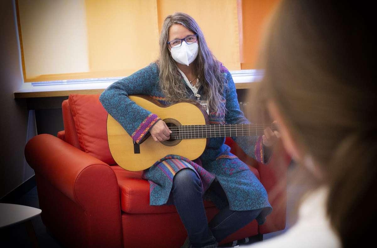 Singen ist wegen Corona nicht erlaubt, und so summt Sabine Rachl unter ihrer Maske zum Spiel  der Gitarre. Foto: Ines Rudel