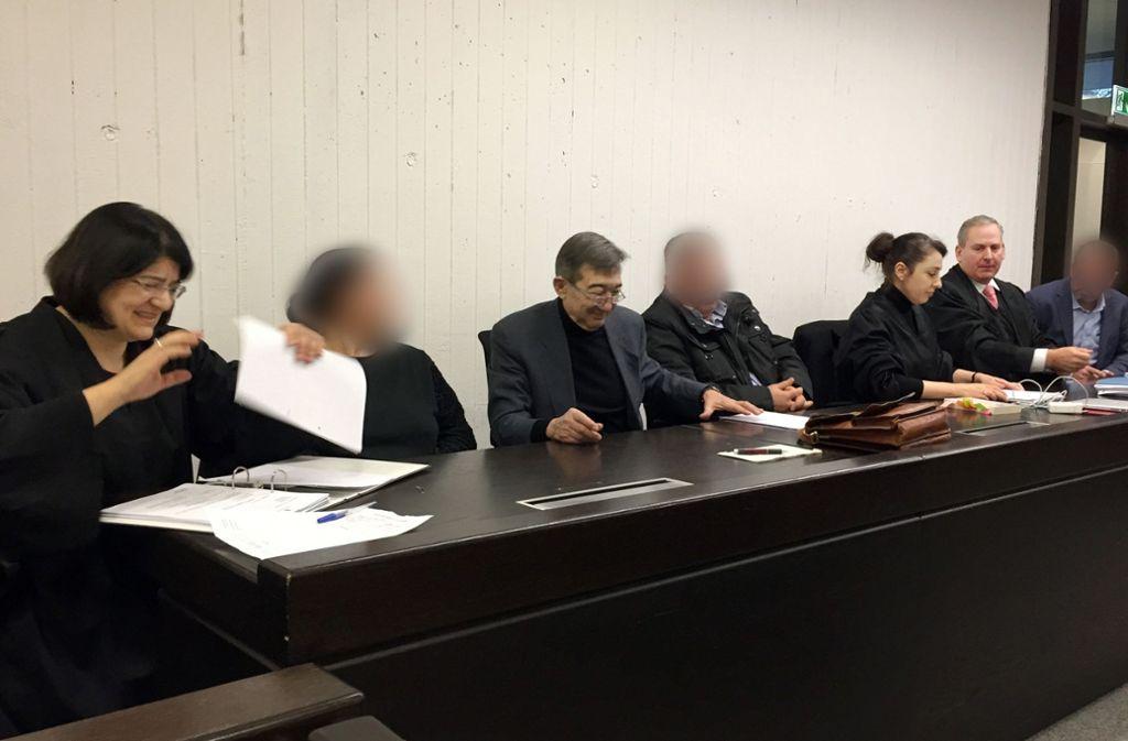 Die drei Angeklagten (gepixelt) beim Prozessauftakt in Stuttgart mit ihren Anwälten. Foto: dpa