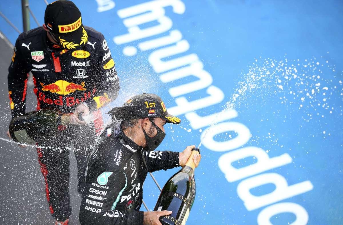 Champagnerdusche mit Maske: Lewis Hamilton (rechts) und Max Verstappen feiern ihre Plätze 1 und 2. Foto: AP/Bryn Lennon
