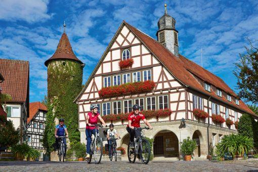 Liebliches Taubertal: Radfahrer vor dem schmucken Rathaus in Niederstetten.
