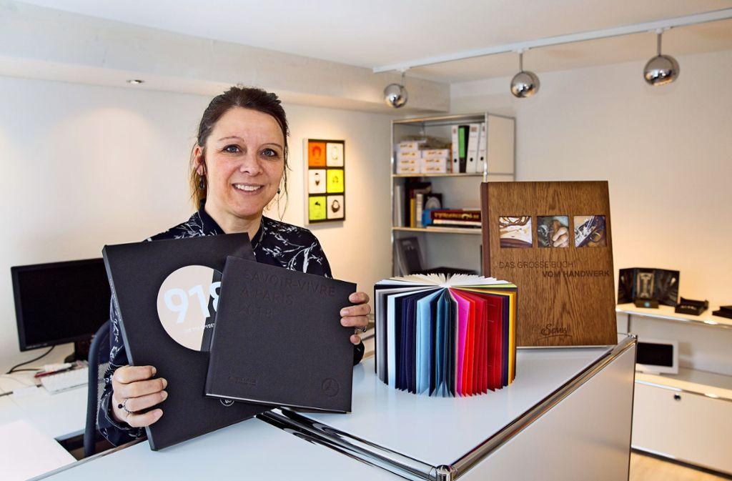 Britta Zapletal zeigt aufwendigeEinbände und Materialien, die typisch fürs Buchbinderhandwerk sind. Foto: Ines Rudel