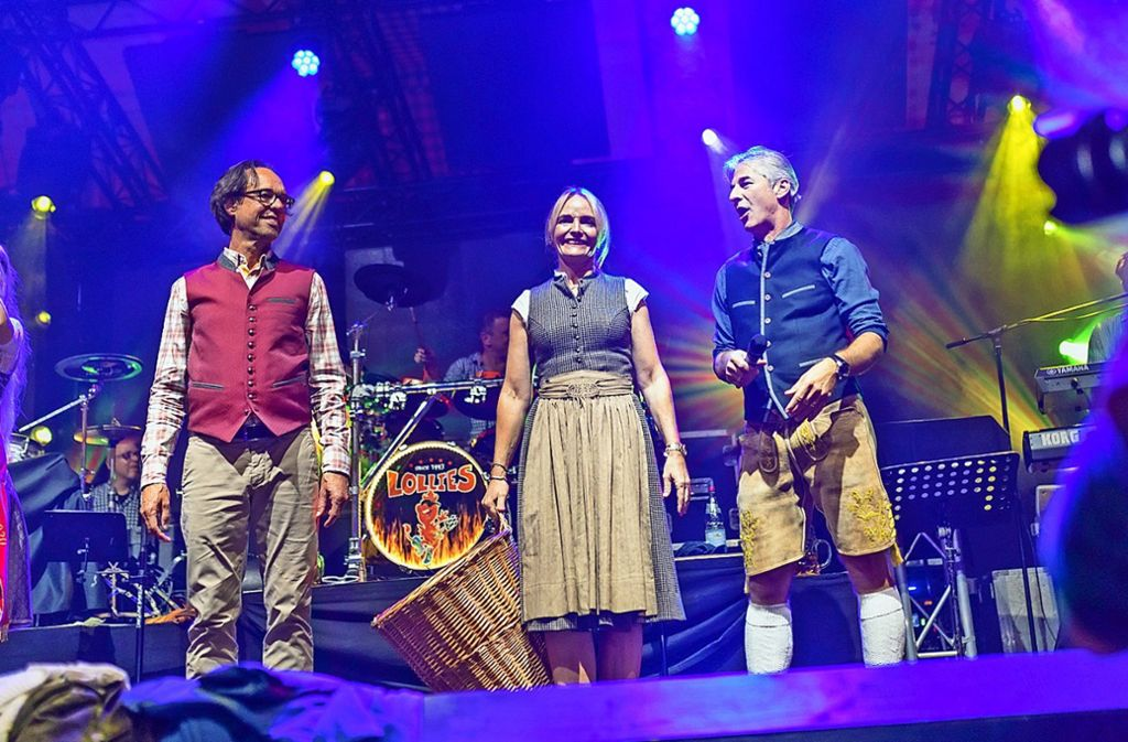 Kabarettist Christoph Sonntag (links) mit den Festwirten Daniela und Karl Maier am Sonntagabend auf der Bühne des Göckelesmaier-Zelts. Foto: Andreas Engelhard