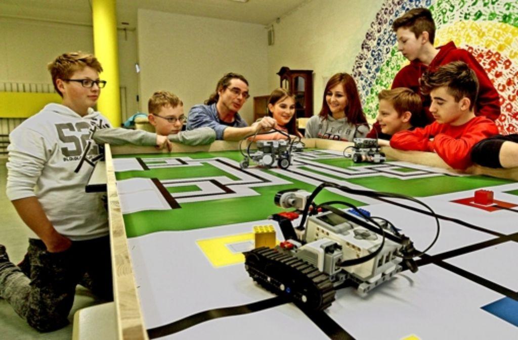 Stephan Schmoll (Dritter von links) probiert mit den Schülerteams die Roboter auf dem Parcourtisch aus. Foto: factum/Bach