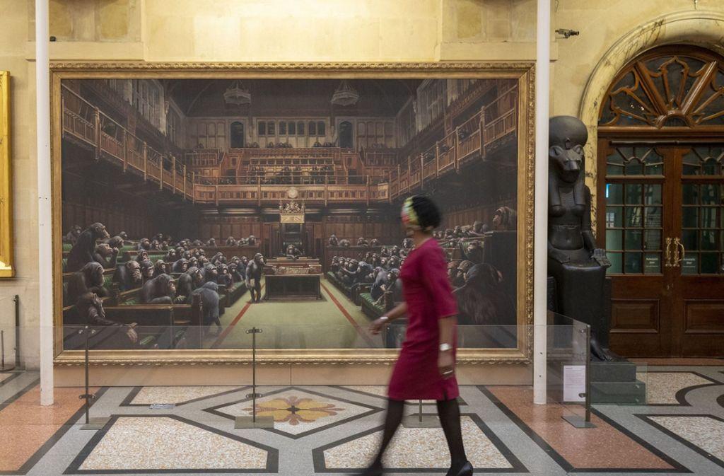 """Eine Besucherin geht an dem Gemälde mit dem Titel """"Devolved Parliament"""" des Graffitikünstlers Banksy im Bristol Museum vorbei. Das Gemälde zeigt das britische Unterhaus von Schimpansen besetzt. Foto: PA Wire"""