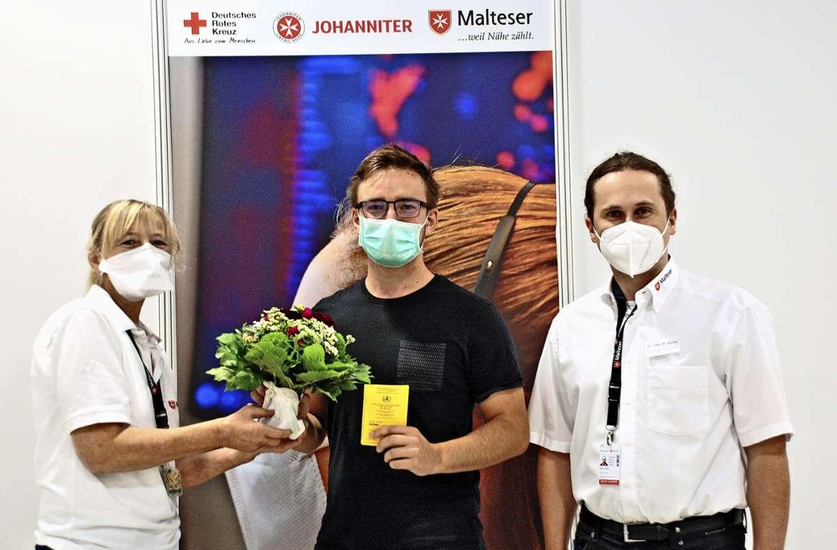 Leon Müller (Mitte) ist der 100 000. Impfling im Esslinger KIZ, die Schichtleiterin Uta Unterberger und der ärztliche Direktor Markus Müller beglückwünschen ihn. Foto: /Peter Stotz
