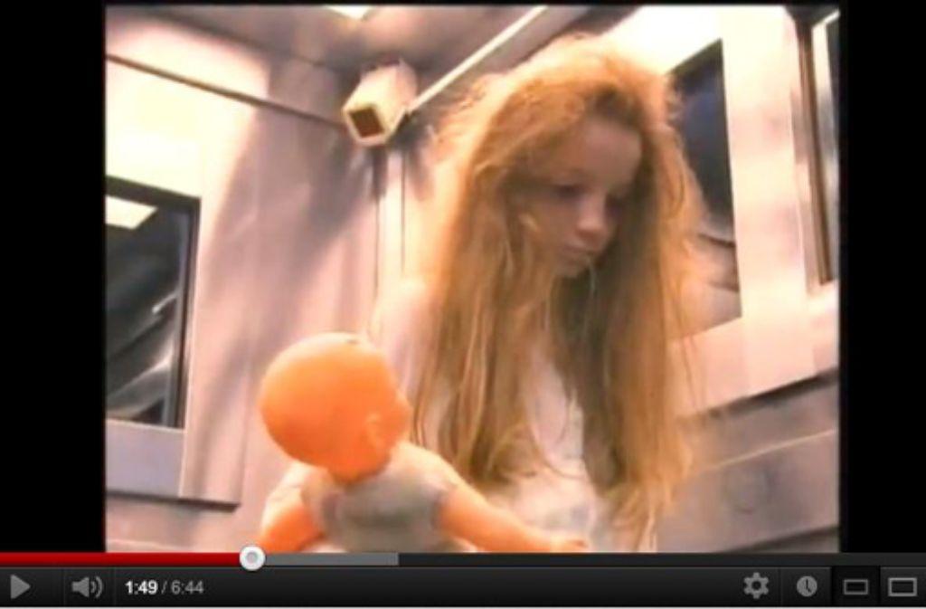 Das Mädchen mit der Puppe sorgt im Aufzug für Panik. Foto: Youtube.com/Screenshot