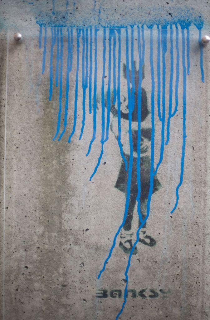 """Anschlag In Hamburg wurde Banksys Schablonengraffito """"Bomb Hugger"""" von einem unbekannten Täter zerstört, der mit blauer Farbe das Wort """"Grafitti"""" und eine Linie oberhalb des Bildes gesprüht hatte.  Foto: dpa"""
