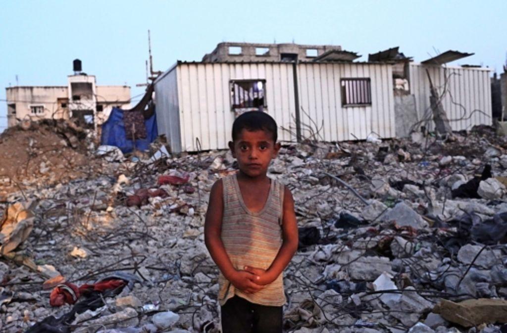 Der fünfjährige Mohammed Azam Al-Massr inmitten von Schuttbergen: Das Gebäude ist in den Auseinandersetzungen im Sommer 2014 zerstört worden. Foto: dpa