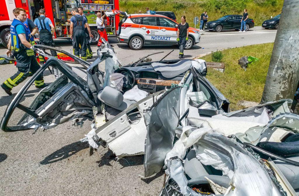Helfer stehen nach einem Verkehrsunfall hinter dem Wrack eines Autos auf einer Landstraße. Foto: Julian Buchner/Einsatz-Report24/
