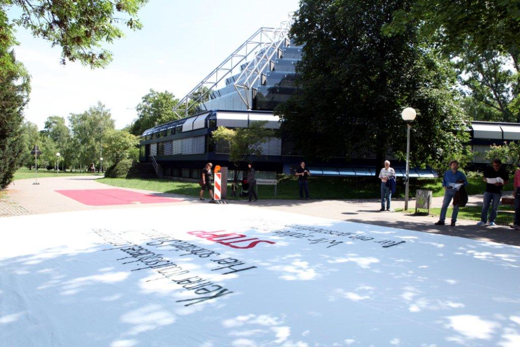 Vor dem Stuttgarter Planetarium haben die so genannten Parkschützer am Freitagvormittag ein riesiges Banner entrollt. Foto: Beytekin