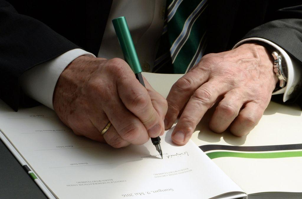 Jetzt ist es amtlich: Winfried Kretschmann unterschreibt den Koalitionsvertrag. Foto: DPA
