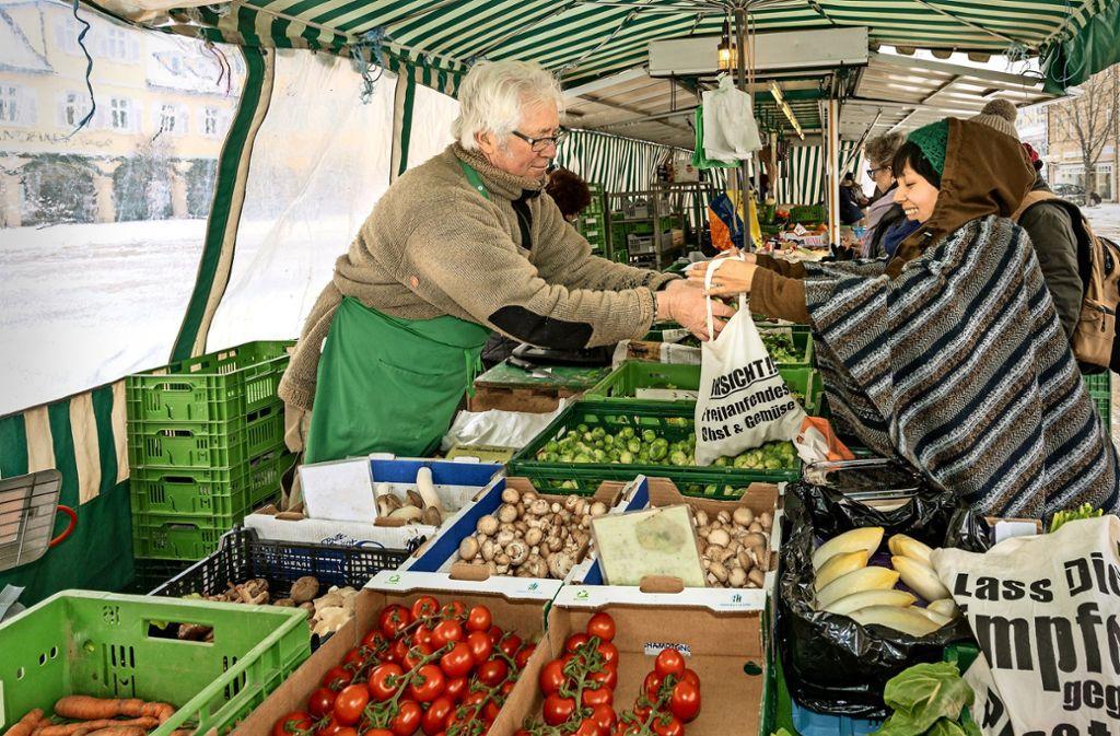 Katja Nguyen Thanh beim Einkauf auf dem Markt in Ludwigsburg. Die Tüten für Obst und Gemüse bringt sie selbst mit. Der Händler Eberhard Klotz   füllt sie gern. Foto: factum/Weise
