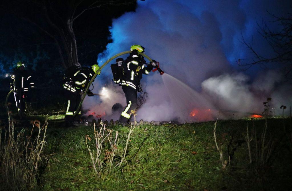 Die Feuerwehrleute beim Löschen der Gartenhütte. Foto: SDMG