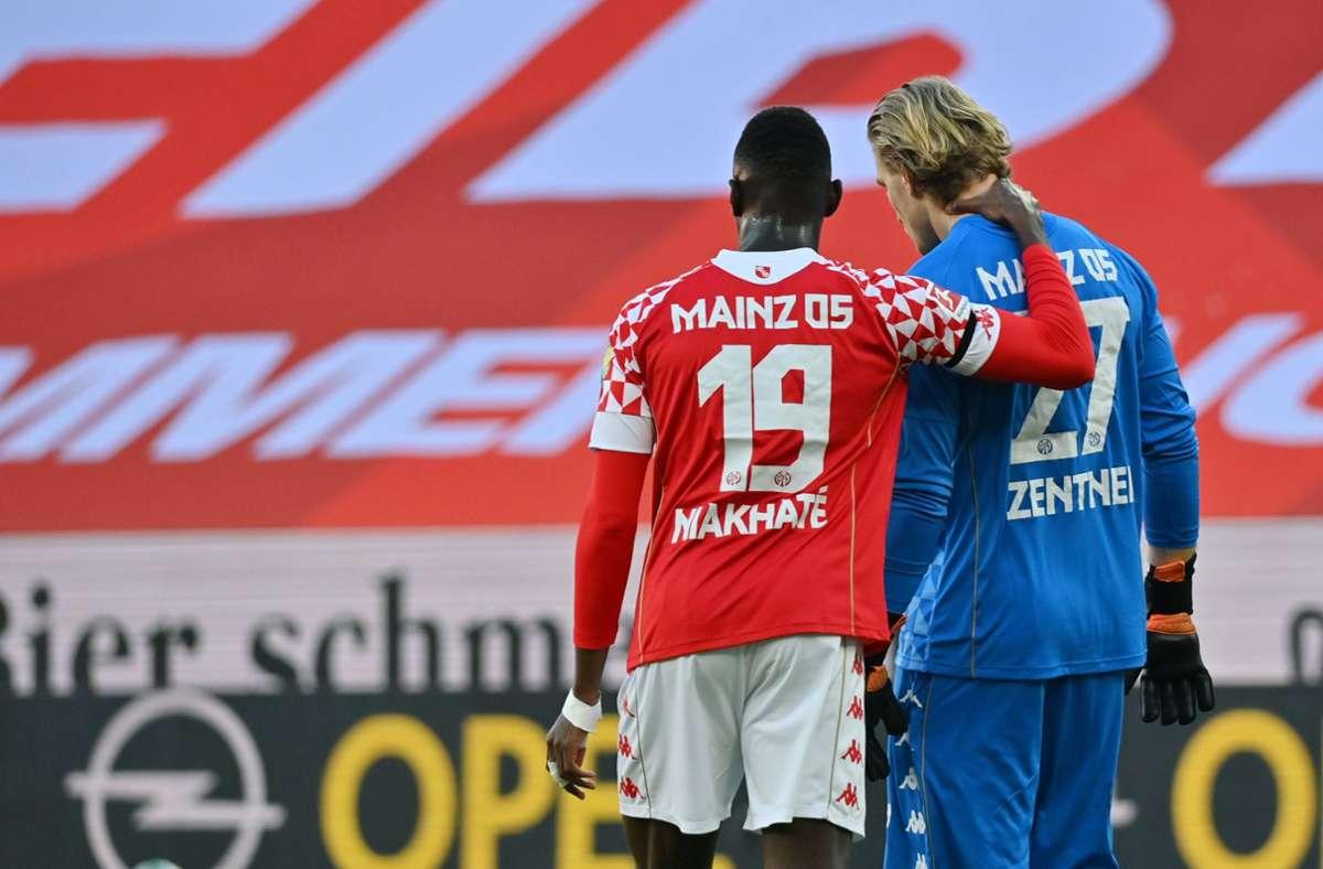 Der Mainzer Spieler Moussa Niakhate (l.) tröstet nach dem Gegentreffer zum 0:1 Torwart Robin Zentner. Foto: dpa/Torsten Silz