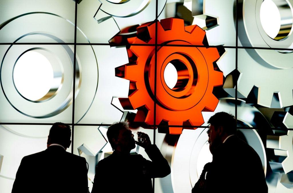 Messebesucher in Hannover stehen vor einem Display mit Zahnrädern Foto: dpa