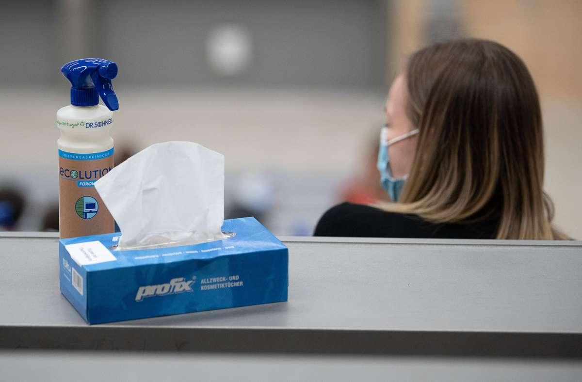 Eine Box mit Papiertüchern und eine Sprühflasche mit Desinfektionsmittel steht neben einer Studentin  der Universität Hohenheim. Foto: dpa/Sebastian Gollnow