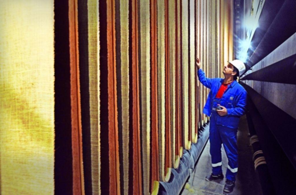 Ein DLW-Mitarbeiter in Delmenhorst kontrolliert den Zustand des frisch produzierten Linoleum-Fußbodenbelages. Foto: dpa