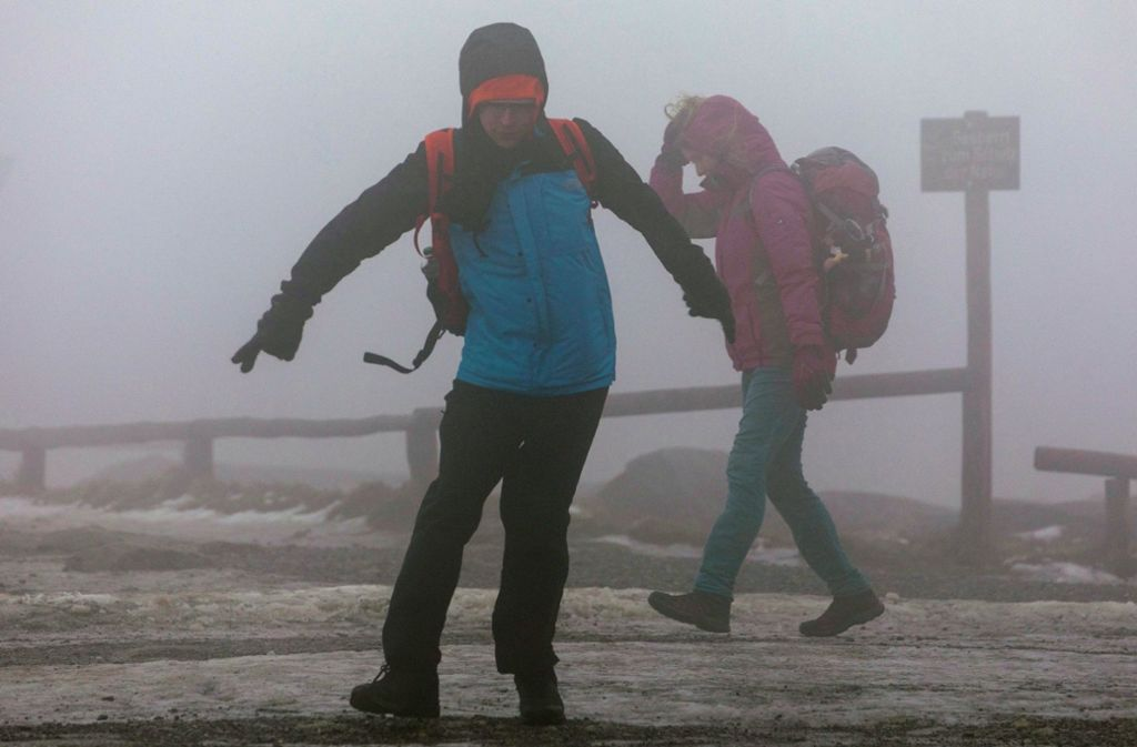 Touristen kämpfen gegen die Windböen auf dem Brocken. Der Deutsche Wetterdienst (DWD) hat für weite Teile Deutschlands die zweithöchste Unwetterwarnstufe wegen des Sturmtiefs «Sabine» herausgegeben. Foto: dpa/Bernd März
