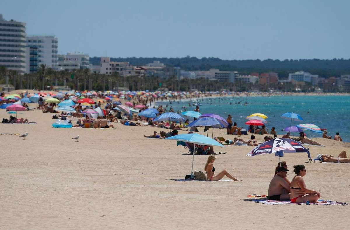 Spanien, Palma: Menschen sonnen sich am Strand El Arenal. Nach wochenlanger Corona-Pause können Urlauber wieder auf die Insel reisen. Foto: dpa/Clara Margais