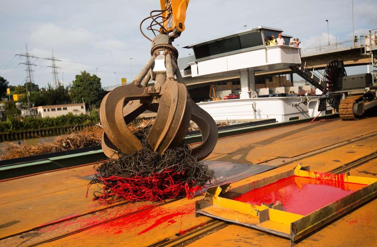 """Spektakulär: Beim Festival """"Drehmomente"""" bemalte vor zwei Jahren ein Bagger im Plochinger Hafen Metallplatten mit roter Farbe. Foto: Ines Rudel"""