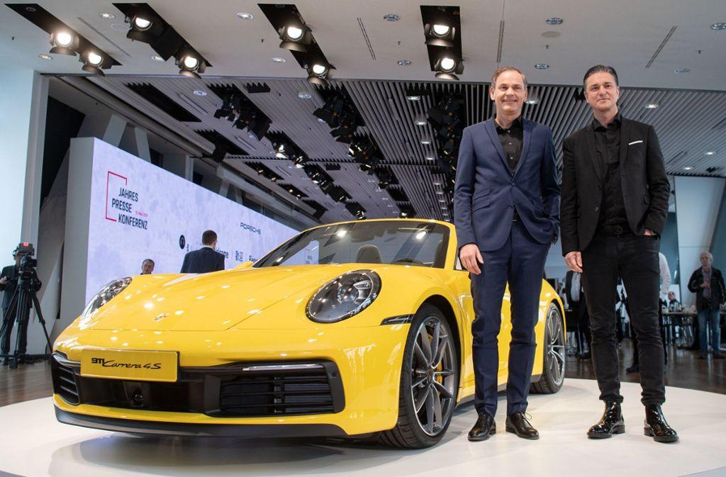 Oliver Blume, Vorstandsvorsitzender der Porsche AG (l.) und Lutz Meschke, Finanzvorstand der Porsche AG, posieren vor der Bilanz-Pressekonferenz vor einem Porsche 911 Carrera 4S Cabrio. Foto: dpa