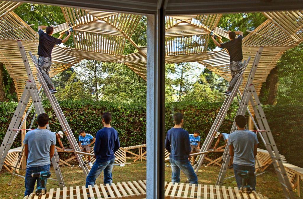 Vier Syrer und drei Afghanen arbeiten an einem Pavillon für den Jugendtreff. Foto: Frank Eppler