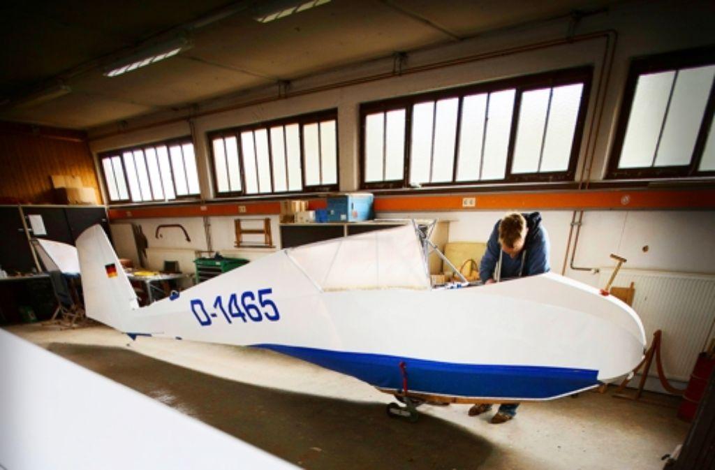 Christian Sorg arbeitet in der Werkstatt der Welzheimer Fliegergruppe im Cockpit des frisch restaurierten Flugzeug-Oldtimers an den letzten Feinheiten. Foto: Gottfried Stoppel