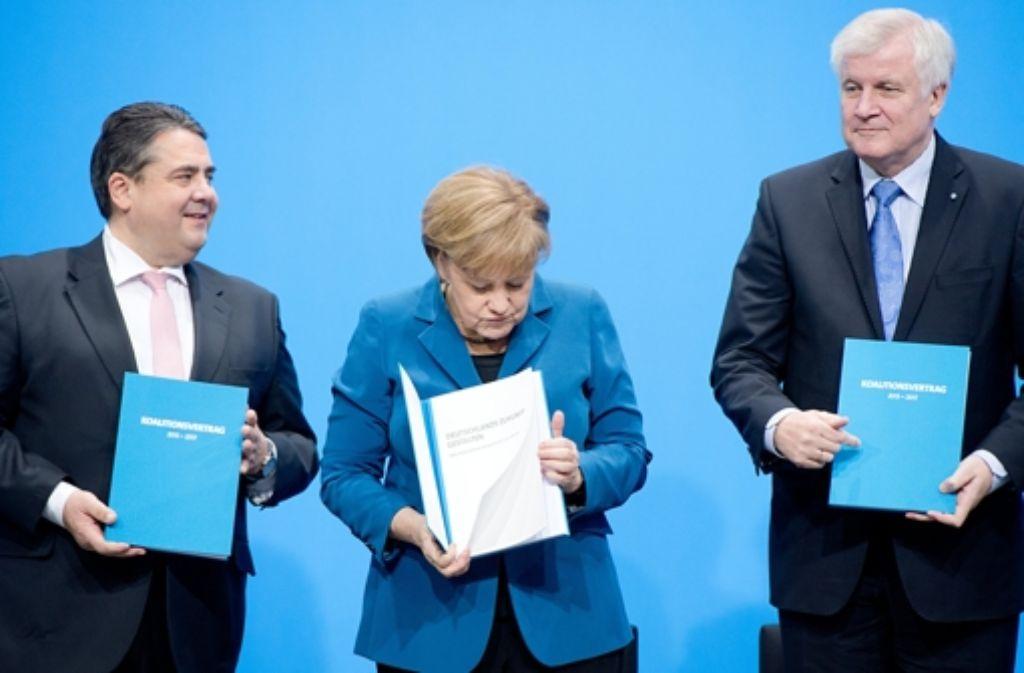 16. Dezember 2013: Kanzlerin Merkel, Wirtschaftsminister Gabriel (links) und CSU-Chef Seehofer halten den frisch unterzeichneten Koalitionsvertrag in den Händen. Foto: dpa