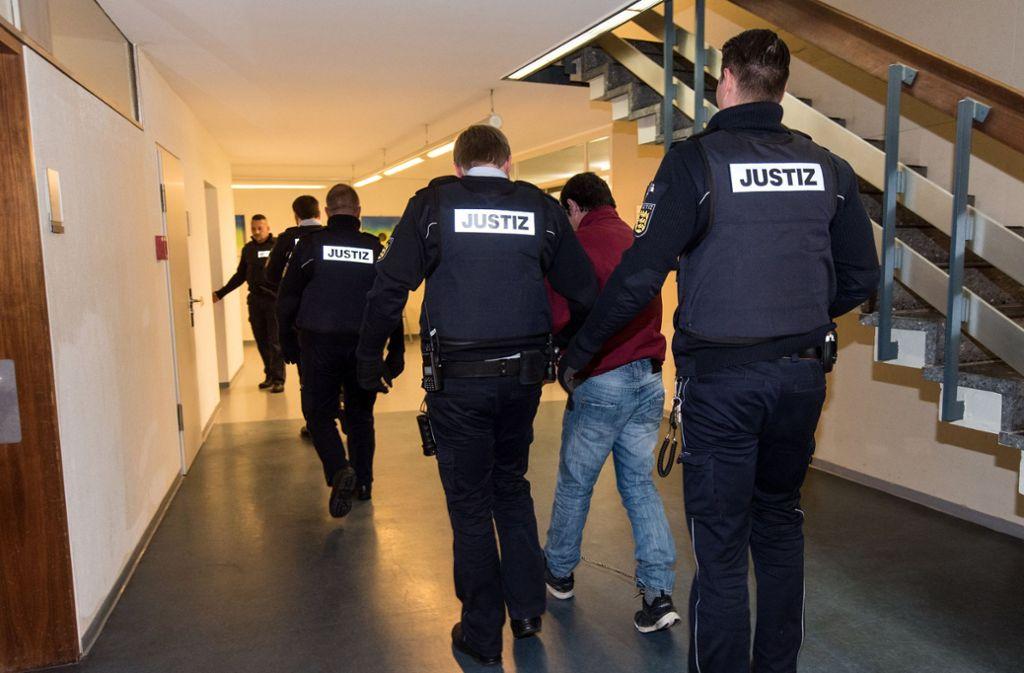 Justizmitarbeiter bringen den Lastwagenfahrer nach der Urteilsverkündung aus dem Sitzungssaal des Landgerichts in Freiburg. Foto: dpa