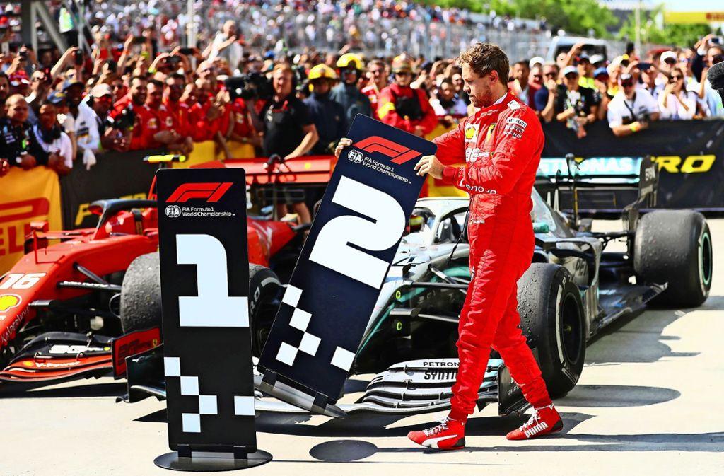 Sebastian Vettel will das Rennergebnis nicht akzeptieren und tauscht die Nummernschilder aus Foto: AFP
