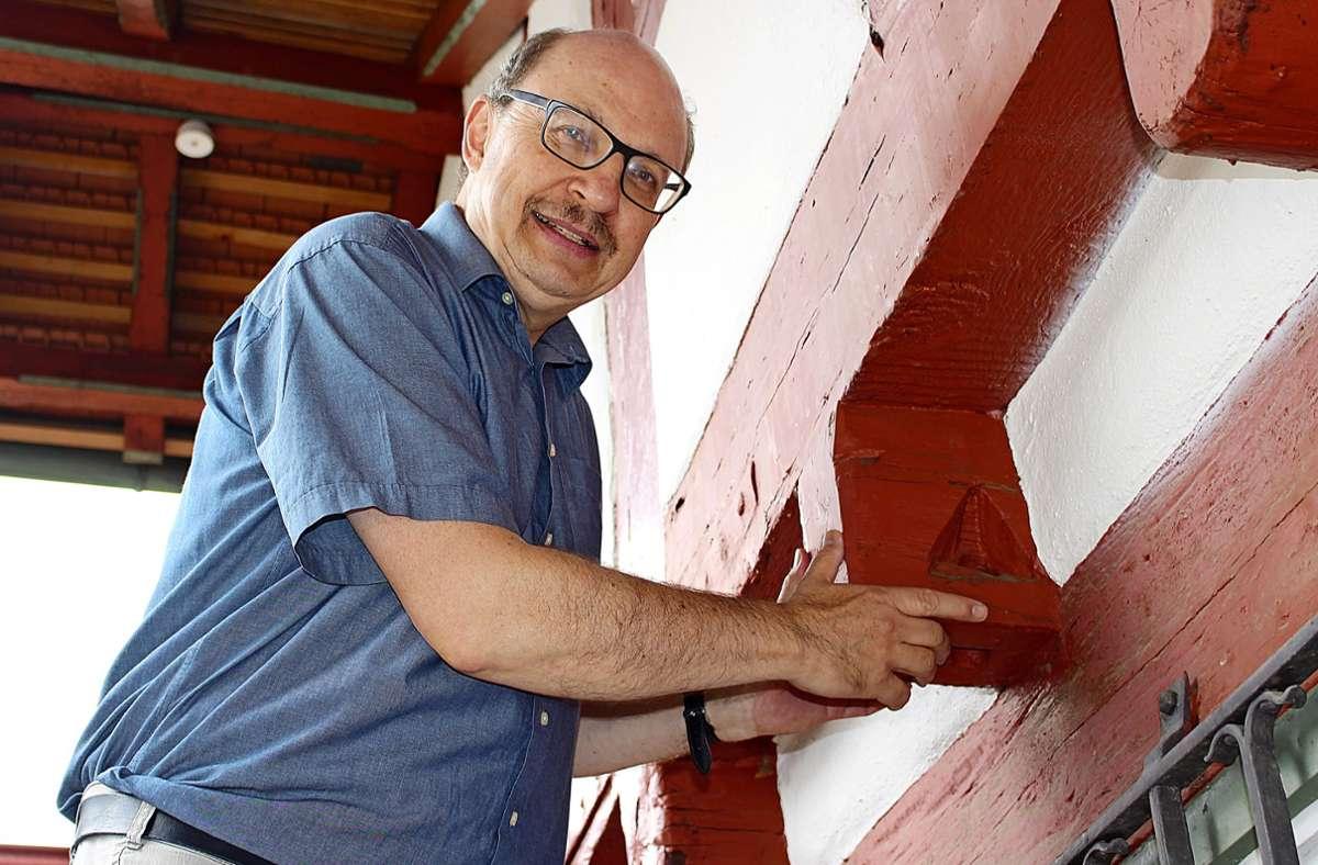 Nikolaus Back, der Filderstädter Stadtarchivar, zeigt am Heimatmuseum sogenannte Flößerlöcher. Sie beweisen: Das Holz fürs Fachwerk kam aus dem Schwarzwald. Foto: /Caroline Holowiecki
