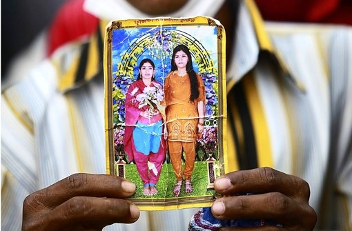 Vermisst unter Trümmern: ein Mann mit dem Foto zweier Näherinnen. Foto: dpa