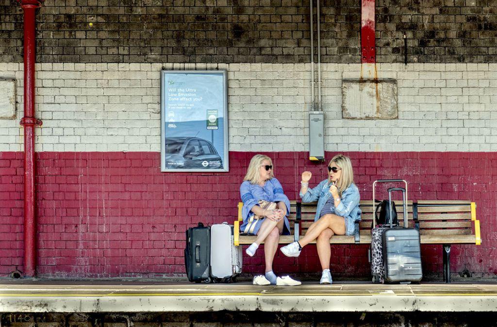 Erst mal die Schuhe aus: zwei Frauen in London überbrücken die Wartezeit – vermutlich an einer U-Bahnstation – mit Reden. Foto: Dieter Leistner
