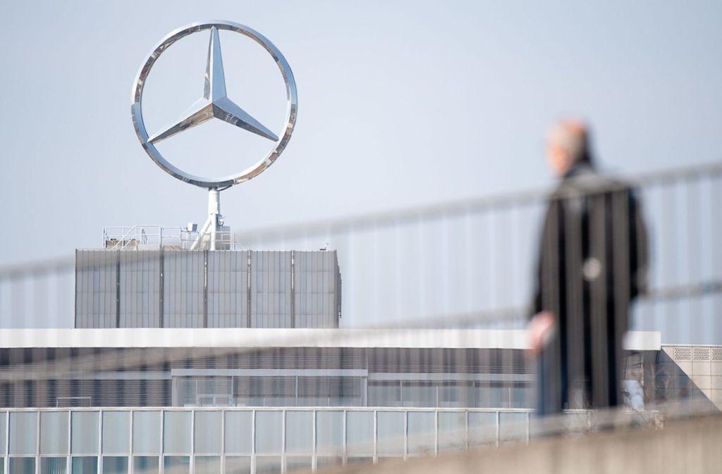 Ein Mitarbeiter von Daimler geht am Mercedes-Benz Werk Untertürkheim zum Schichtwechsel vor einem Mercedes-Stern Richtung Werk. Der Autobauer wird im April Kurzarbeit beantragen. Foto: dpa/Sebastian Gollnow