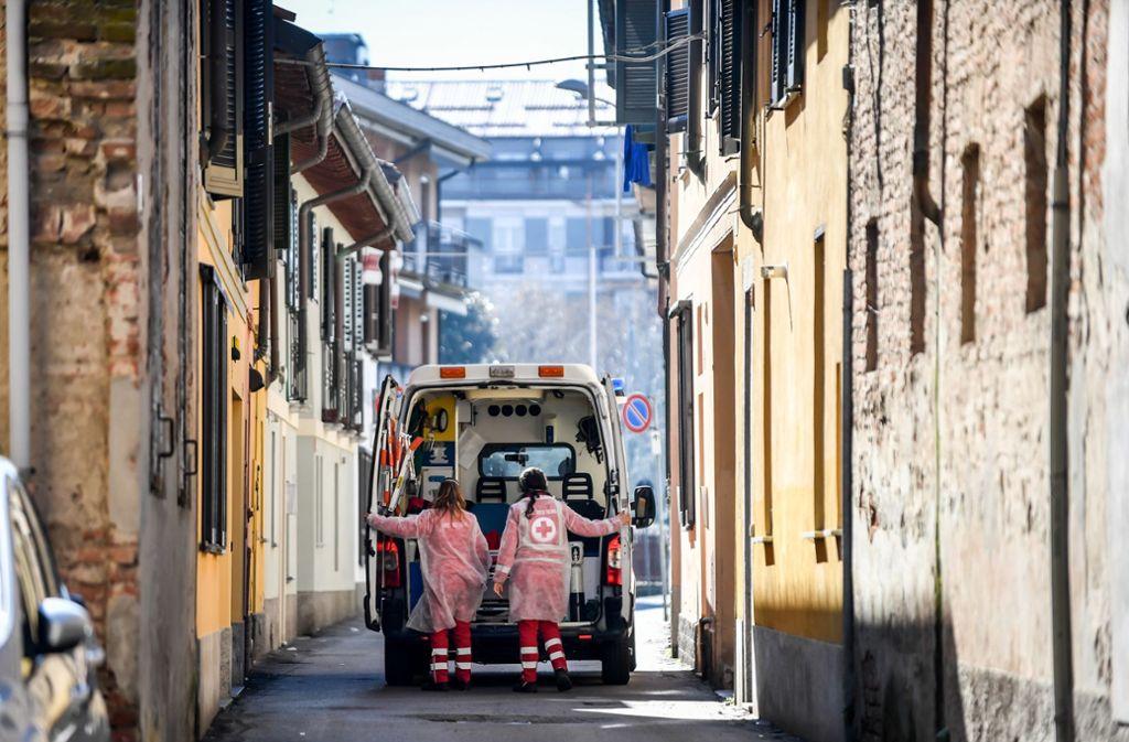 Italien, Codogno: Zwei Rettungsdienstmitarbeiterinnen öffnen die Türen eines Krankenwagens. Foto: dpa/Claudio Furlan