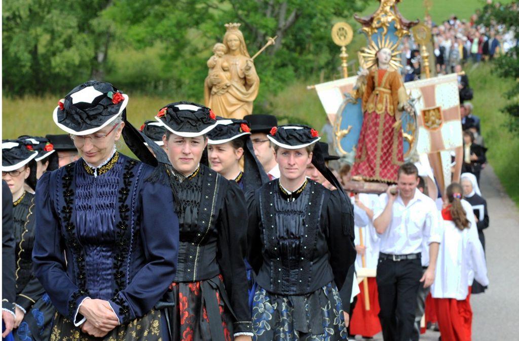 In der traditionellen Tracht von St. Peter im Schwarzwald begleiten katholische Gläubige die Fronleichnamsprozession. Nach einem Festgottesdienst ziehen sie unter Gebet und Gesang von Station zu Station um den Ort im Hochschwarzwald. Foto: dpa