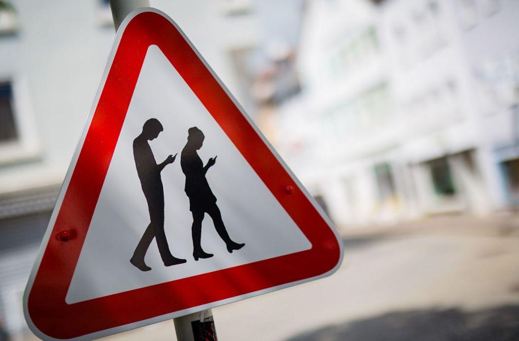Wer ständig aufs Handy schaut, sollte seine Umgebung nicht gänzlich vergessen. Foto: dpa/Christoph Schmidt
