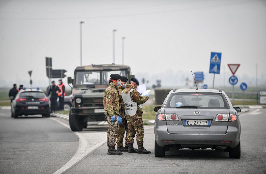 Soldaten mit Atemschutzmaske kontrollieren einen Autofahrer an einer Straßensperre vor der roten Zone von Turano Lodigiano. Foto: dpa/Claudio Furlan