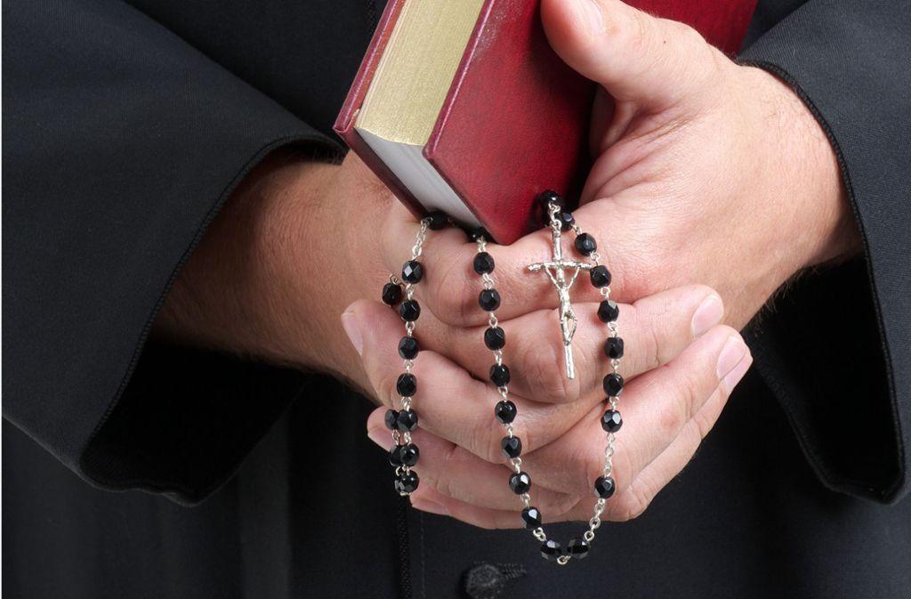 Ein katholischer Priester mit Bibel und Rosenkranz Foto: Fotolia