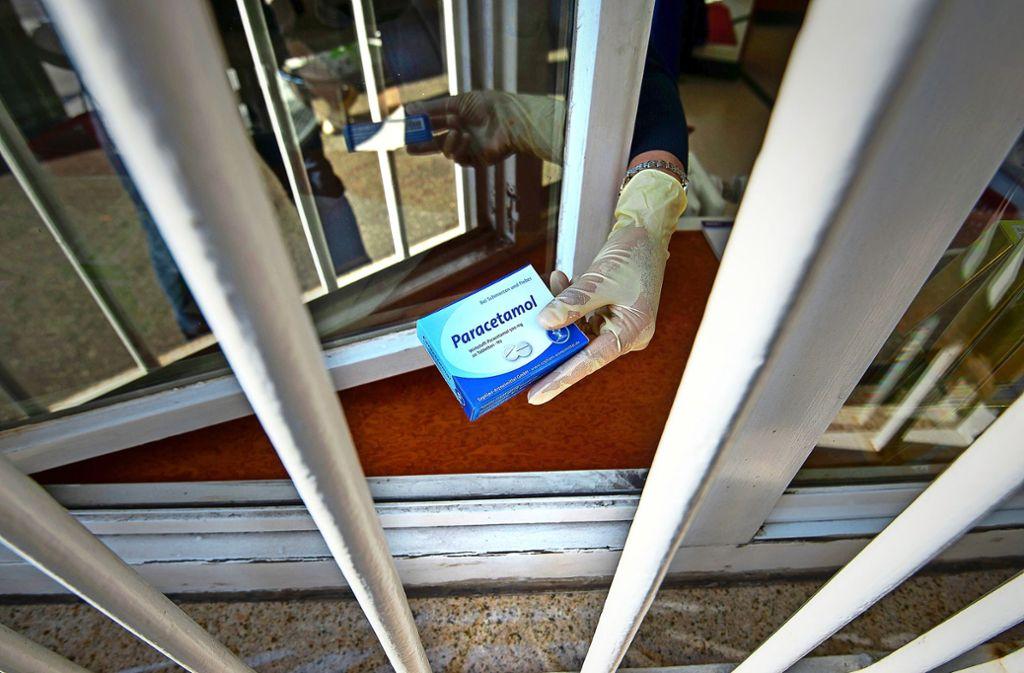 In der Charlotten-Apotheke am Olgaeck in Stuttgart reicht eine Mitarbeiterin eine Packung Paracetamol durchs Verkaufsfenster. Die Ladentür bleibt in diesen Tagen geschlossen. Foto: Lichtgut/Leif Piechowski