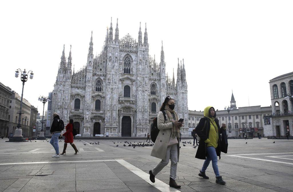 Eine Frau trägt eine Atemschutzmaske, während sie über den weitgehend meschenleeren Platz vor dem Mailänder Dom läuft. Foto: dpa/Luca Bruno