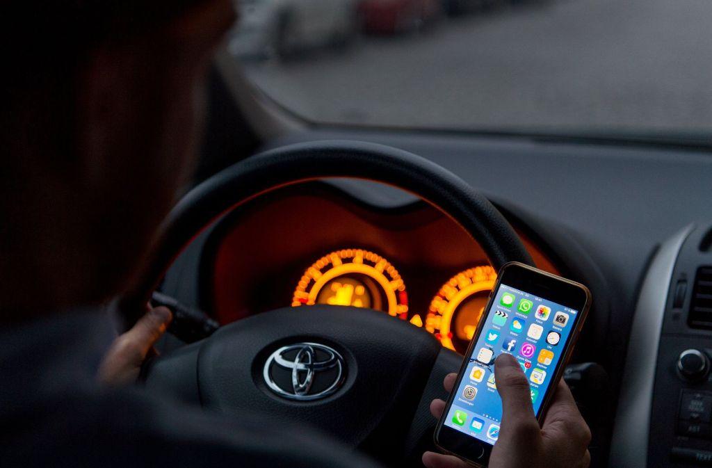 Wer bei Tempo 50 eine Sekunde aufs Handy schaut, fährt 14 Meter blind. Foto: dpa