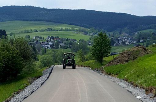 Mann fährt mit Traktor über frisch geteerte Straße