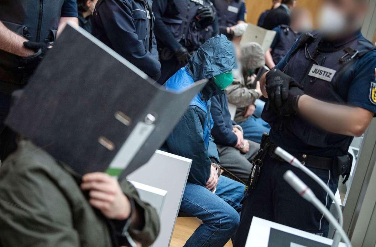 """Einige Angeklagte sitzen kurz vor Beginn des Prozesses gegen die mutmaßlich rechtsterroristische Vereinigung """"Gruppe S."""" in einem Saal im Oberlandesgericht Stuttgart-Stammheim. (Archivbild) Foto: dpa"""