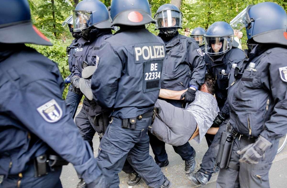 Polizisten tragen bei einer Kundgebung gegen die Corona-Beschränkungen auf der Straße des 17. Juni einen Mann. Foto: dpa/Christoph Soeder